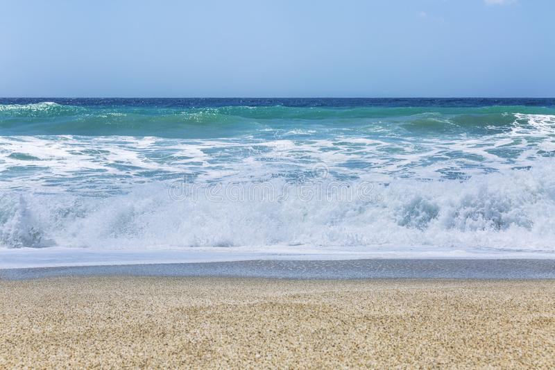 Turkooise strook van het overzees met golven op een zandig strand Duidelijke blauwe hemel Achtergrond Mooi rustig landschap stock foto's