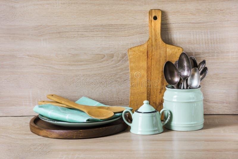 Turkos och trätappninglerkärl, bordsservis, dishwareredskap och material på träbordsskiva Kökstilleben som backgroun arkivbild