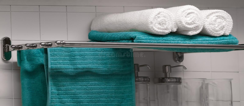 Turkos och vita handdukar på hylla i badrummet royaltyfri foto