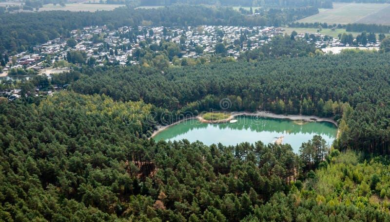 Turkos rektangulär sjö i ett skoglandskap framme av en stor campa plats, rest av att bryta för sand royaltyfri fotografi