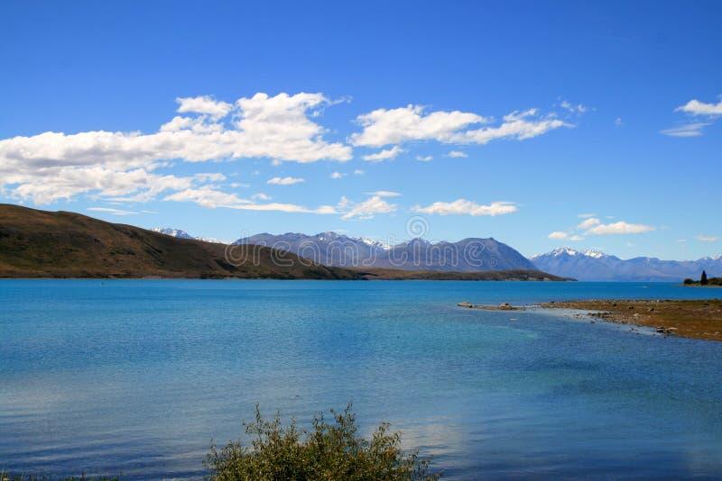 Turkosblå sjö Tekapo som omges av kullar av sydliga fjällängar i tillbaka arkivbild