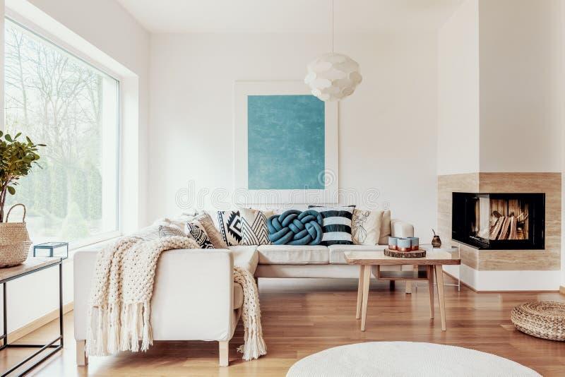 Turkosblått knyter kudden på en beige hörnsoffa och en abstrakt affisch på en vit vägg i en modern vardagsruminre arkivbild
