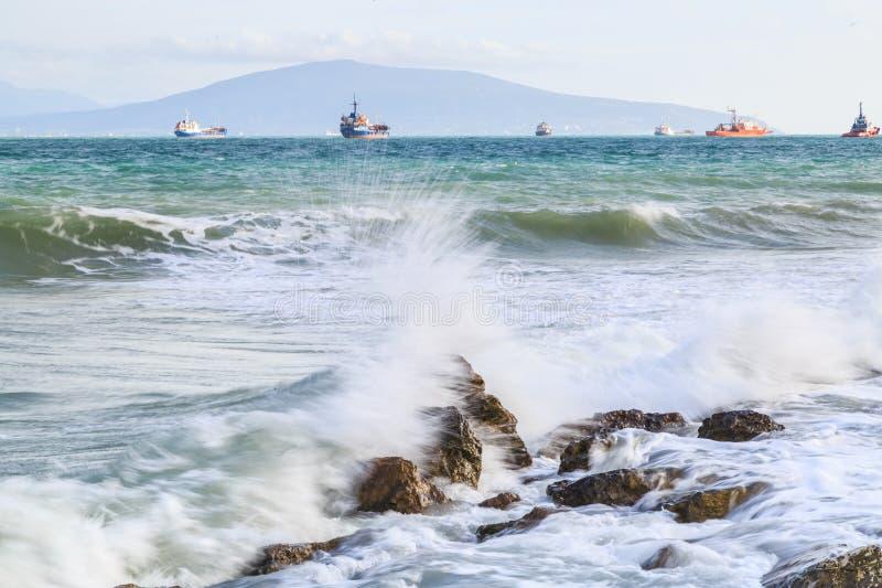 Turkoshavsvågor bryter mot stenar på bakgrund av skepp som ankras på horisonten under en storm royaltyfri fotografi