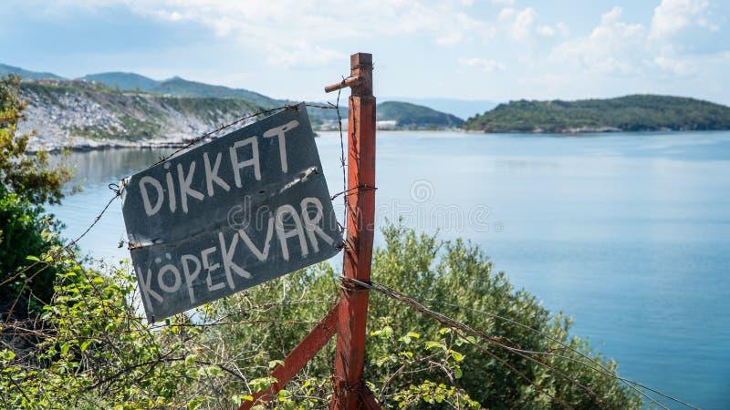 Turks bord dat Beware van de waarschuwing van de Hond vertaalt, op een kettinglink fence achtergrond royalty-vrije stock foto