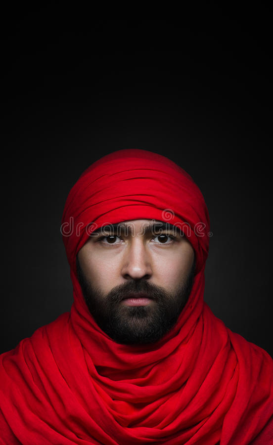 Turks en Arabisch thema: mooie Moslimmens met een baard in een rode die headscarf op een zwarte achtergrond in studio wordt geïso royalty-vrije stock foto's