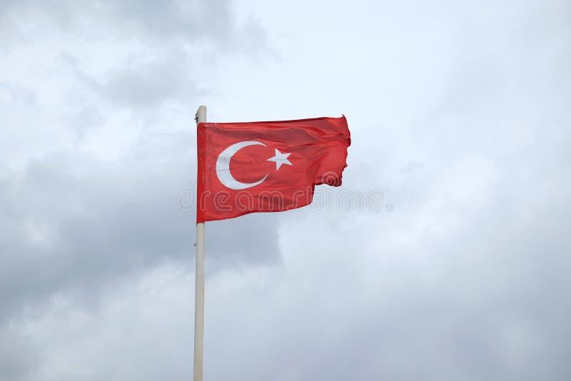 Turks rood vlagverstand met ster en halve maan die op sombere dag golven stock foto's