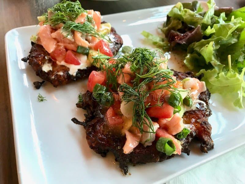 Turks Voedsel Fried Zucchini Mucver met Gerookte Zalm, Tomaten en Dille stock afbeeldingen