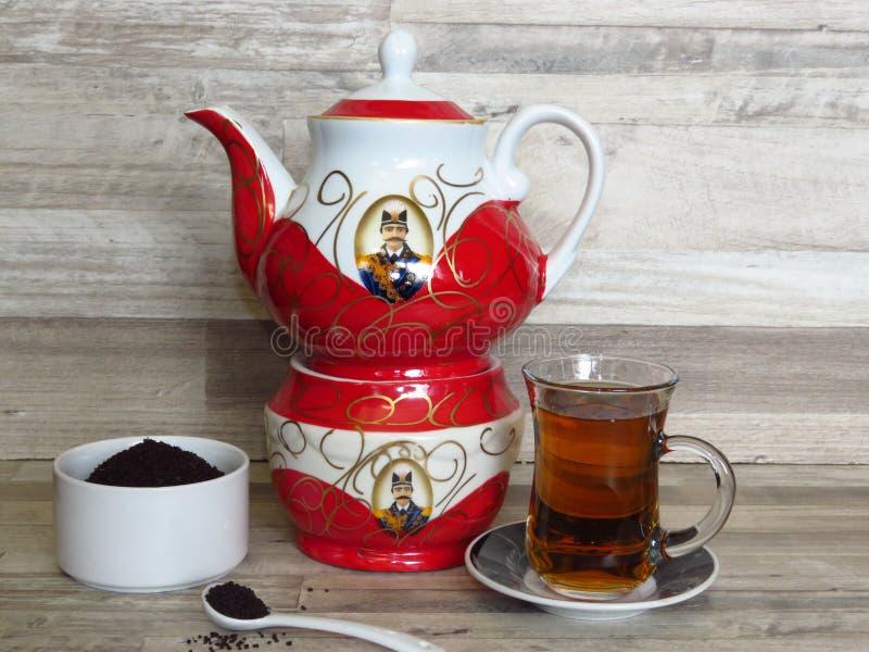 Turkse, Iraanse, Perzische zwarte thee in glas Chai De rode Iraanse porseleintheepot en het Zwarte theepoeder in een wit porselei royalty-vrije stock afbeeldingen