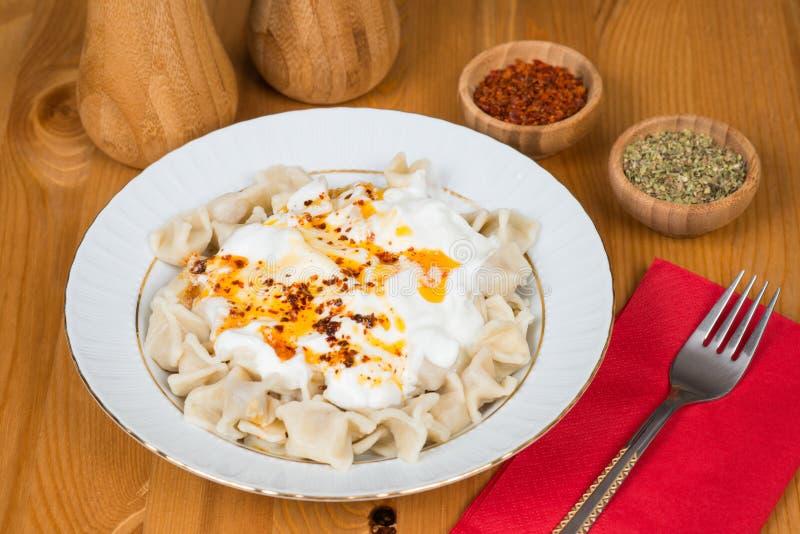 Turkse Manti (ravioli) op plaat met Spaanse peper, boter, saus, yoghurt en munt stock foto's