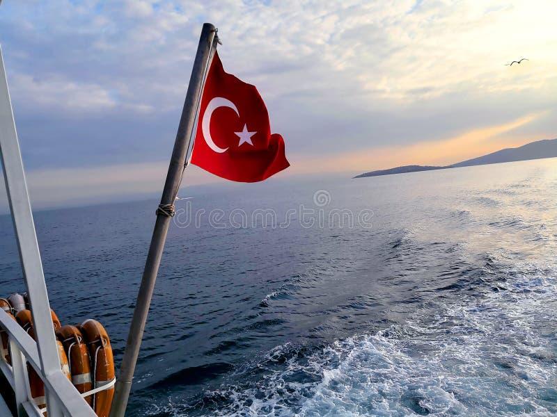Turkse vlag die tijdens het vertrek van het eiland van prinsessen in Istanboel bij zonsondergang vliegen royalty-vrije stock afbeeldingen