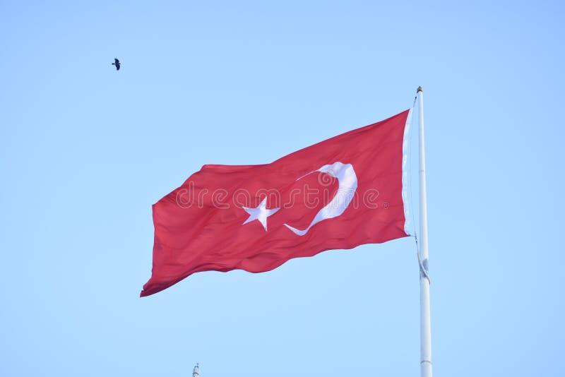 Turkse vlag op vlaggestok die in wind golven stock fotografie