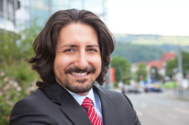 Turkse zakenman die met kostuum bij camera voor zijn bureau lachen royalty-vrije stock afbeelding