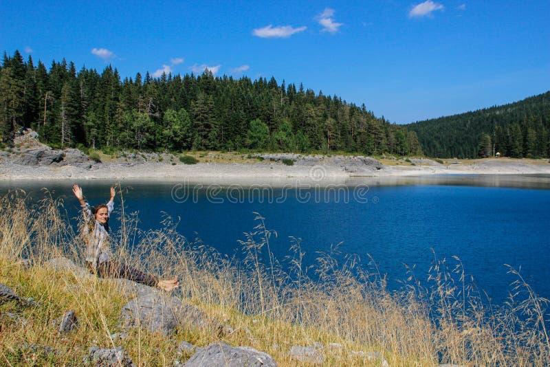 Turkus woda jezioro, sosnowy las i g?ry, Osza?amiaj?co t?o z natury dziewczyny turystycznym obsiadaniem na pla?y obrazy stock