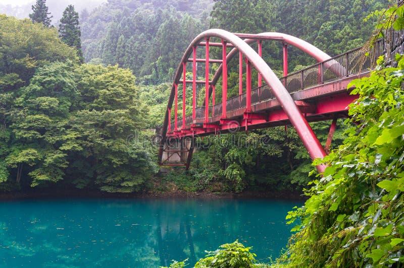 Turkusowa błękitne wody lasowy jezioro z czerwień łuku mostem zdjęcie stock