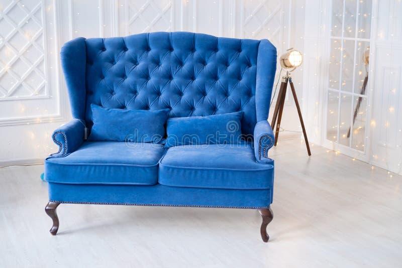 Turkusowego kanapa rocznika błękitna leżanka w białym wnętrzu Stary światło reflektorów i bożonarodzeniowe światła zdjęcie royalty free