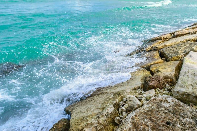 Turkusowy tropikalny wyspa karaibska oceanu wody chełbotanie przeciw wielkim dennym skałom fotografia royalty free