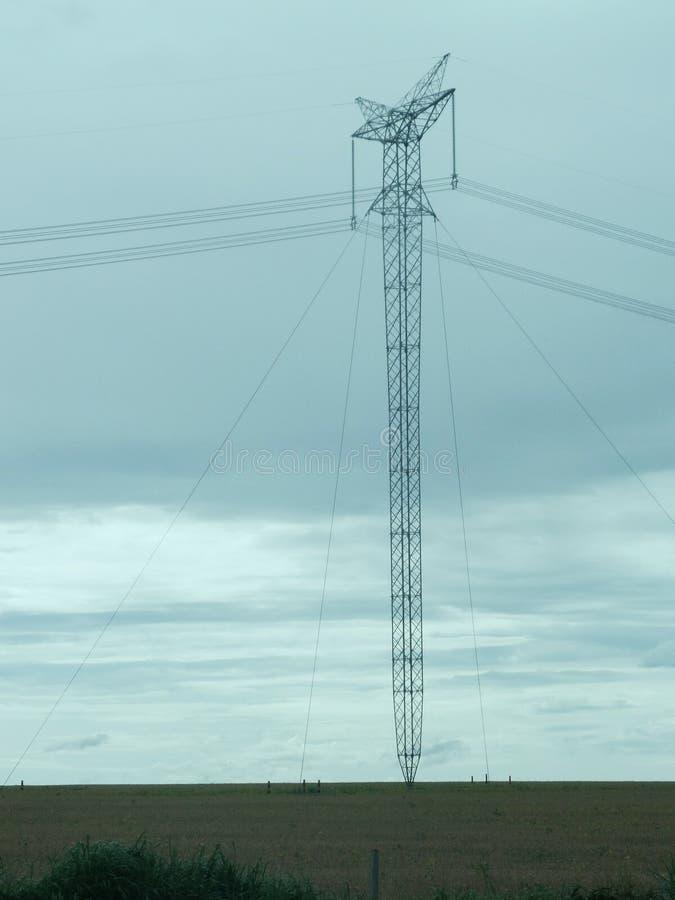 Turm des elektrischen Stroms mitten in einer Sojabohnenplantage stockfotos