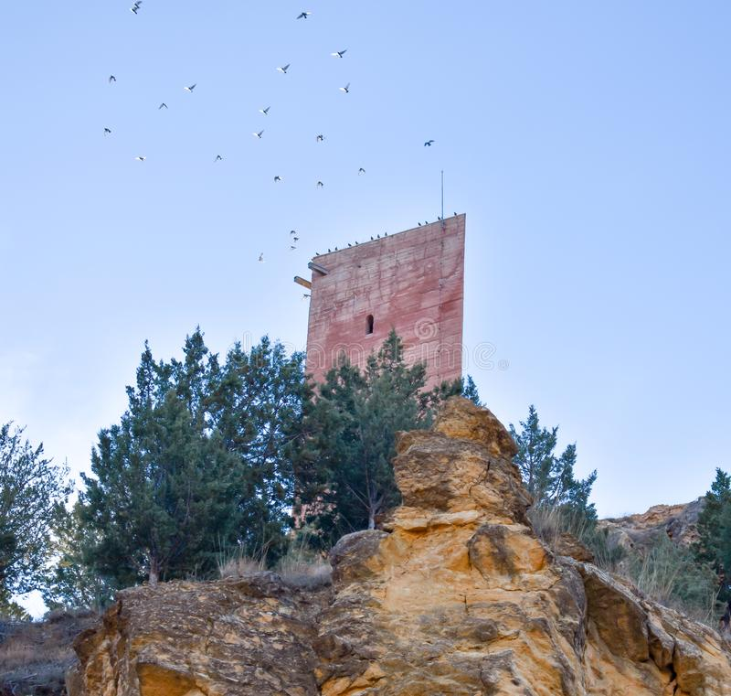 Turm eines alten Schlosses in einem kleinen Dorf nannte Villel in Teruel/in Spanien bei dem Sonnenaufgang morgens Fliegen vieler  stockfotografie