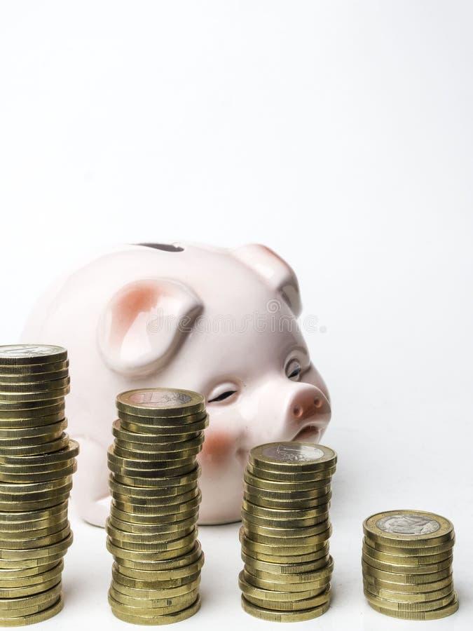 Turm von den Münzen lokalisiert auf weißem Hintergrund mit rosa Schwein, Atelieraufnahme stockfotografie