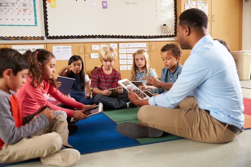 Turma escolar elementar que senta tabuletas de utilização equipadas com pernas transversais fotografia de stock