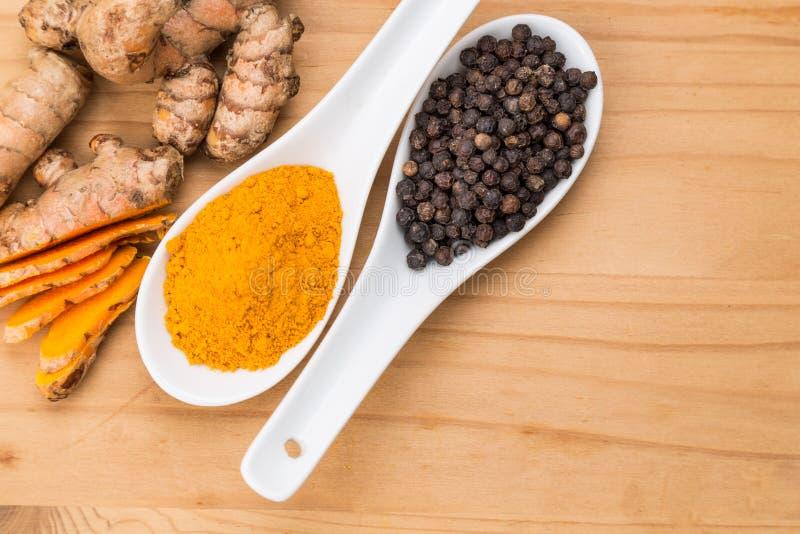 Turmeric οι ρίζες και ο μαύρος συνδυασμός πιπεριών ενισχύουν την κουρκουμίνη αβ στοκ φωτογραφία με δικαίωμα ελεύθερης χρήσης