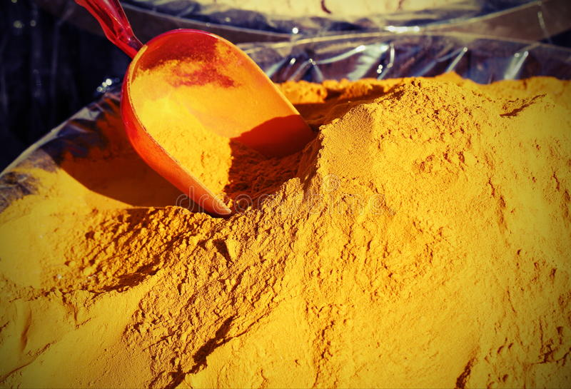 Turmeric Curry powder background and a red bailer. Turmeric Curry powder for sale and a little red bailer stock images