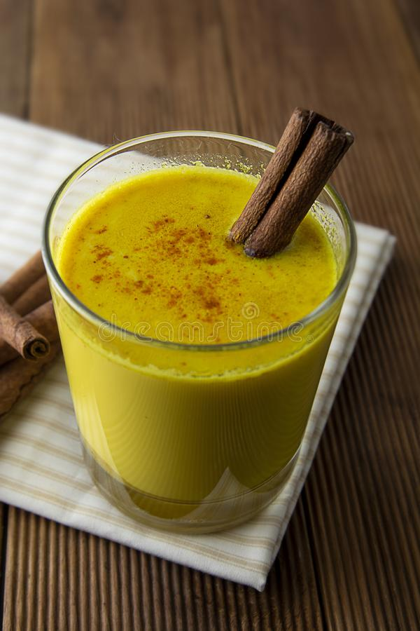 Turmeric Golden Milk. Healthy drink made with turmeric honey and cinnamon. Remedy for many diseases. Rustic wooden background royalty free stock photos