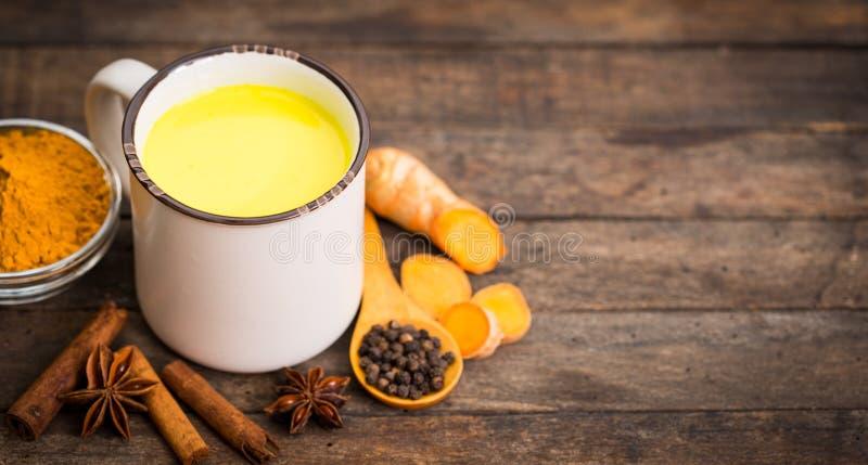 Turmeric golden milk latte with honey and cinnamon stock photo