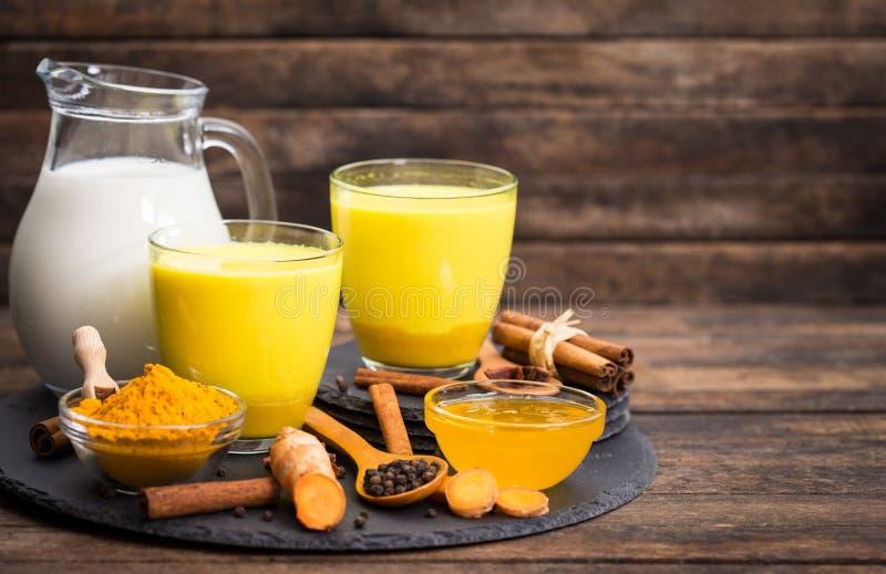 Turmeric golden milk latte with honey and cinnamon stock photography