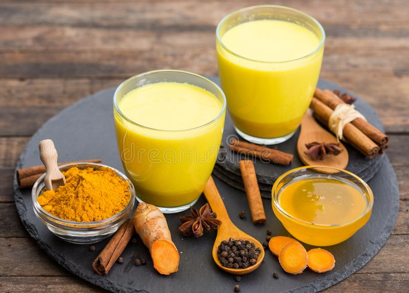 Turmeric golden milk latte with honey and cinnamon stock photos