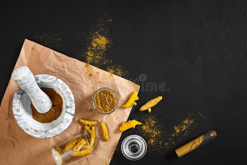 Turmeric Haldi proszek w małym pucharze z surowy całym w marmurowym moździerzu nad czarnym tłem z kopii przestrzenią zdjęcie stock