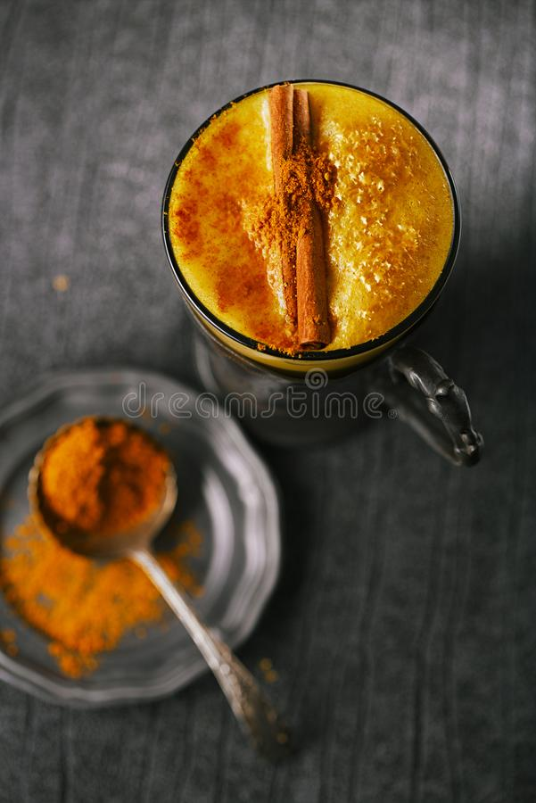 Turmeric latte or golden milk with cinnamon stick and spice mix stock image