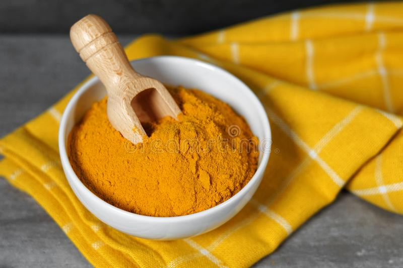 Turmeric Powder Bowl. Turmeric powder healthy spice Asian food closeup of a white bowl with a wooden bailer royalty free stock photo