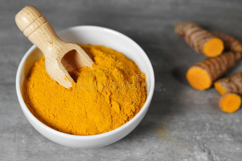 Turmeric Powder Bowl And Roots. Turmeric powder and sliced turmeric roots healthy spice Asian food closeup of a white bowl with a wooden bailer royalty free stock photography
