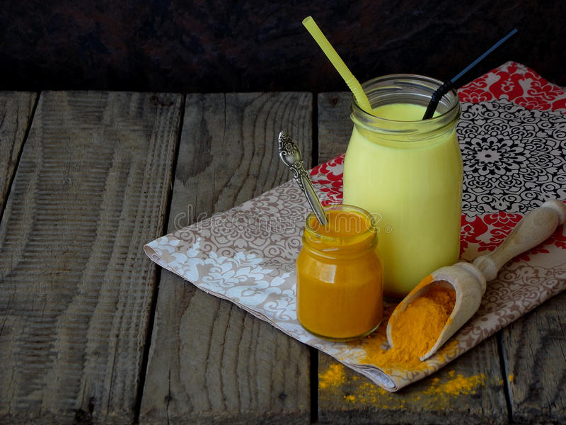 Turmeric powder, paste and latte on wooden background. Ayurvedic healthy golden drink with coconut milk and ghee for beauty. And health. Selective focus. Copy stock image