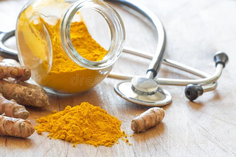Turmeric powder and turmeric roots with stethoscope, natural medicine royalty free stock image
