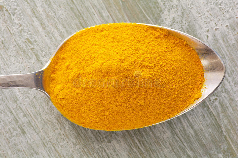 Turmeric powder on a spoon stock image
