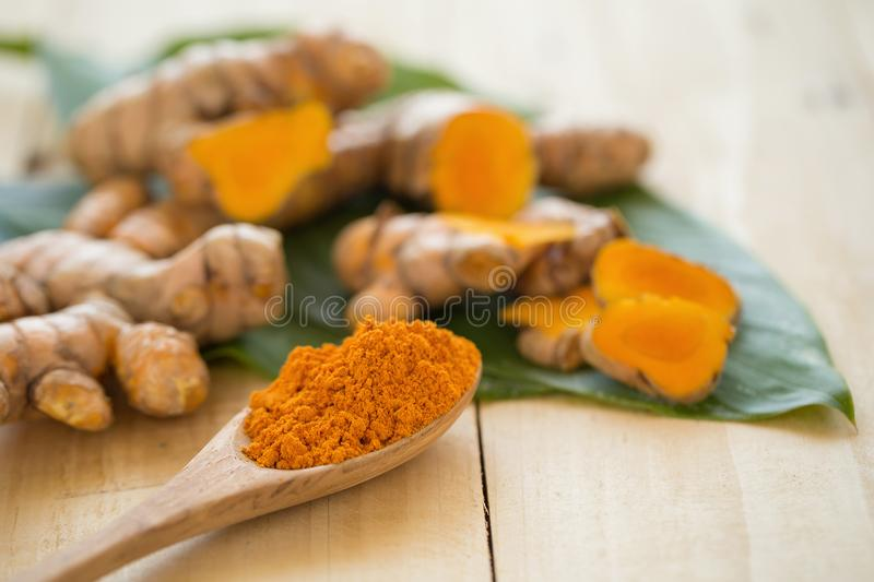 Turmeric powder in a wooden spoon and fresh turmeric on wooden b royalty free stock photo