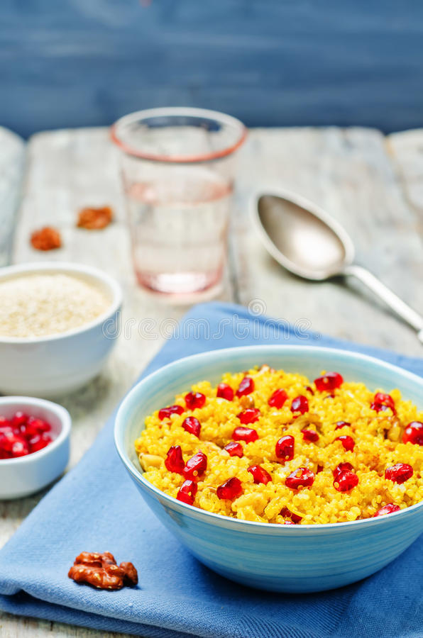 Turmeric quinoa with pomegranate and walnuts. Toning. selective focus royalty free stock photos