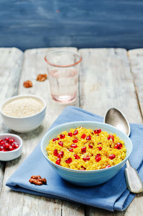 Turmeric quinoa with pomegranate and walnuts. Toning. selective focus stock photography