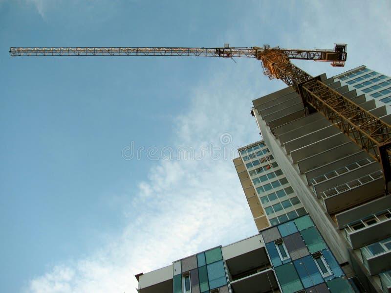 Turmkran befestigte zum konkreten Gebäude während des Baus stockbilder