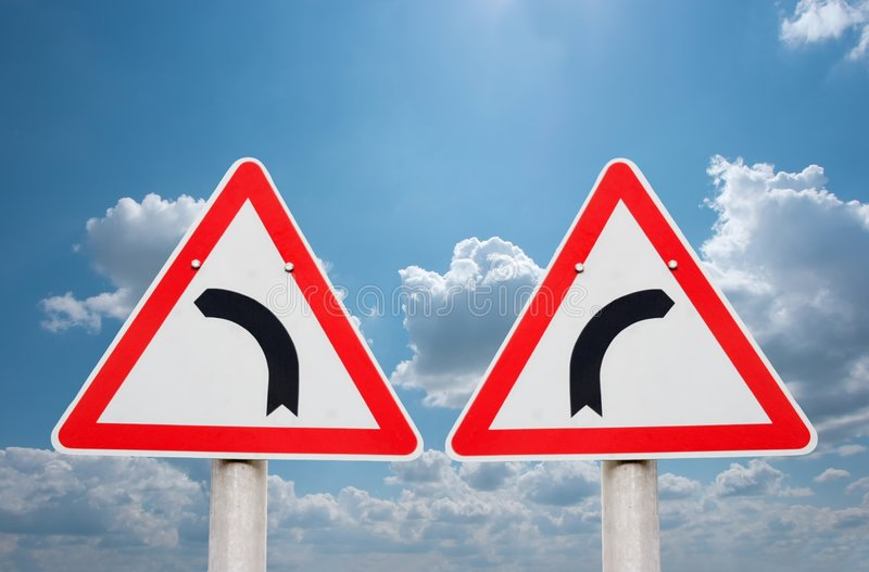 Turn. Ing road traffic signs showing opposite directions royalty free stock photo