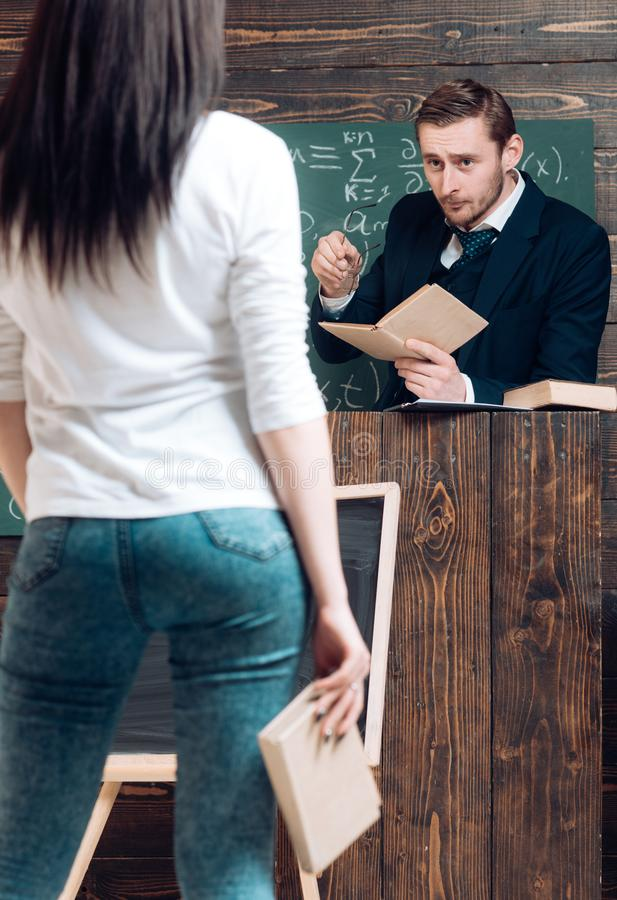 Turn back brunette girl holding book in her hand. Strict teacher looking at his female student while standing at rostrum stock photos