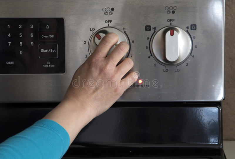 Turn on cooktop. A person is turning on cooktop royalty free stock photos