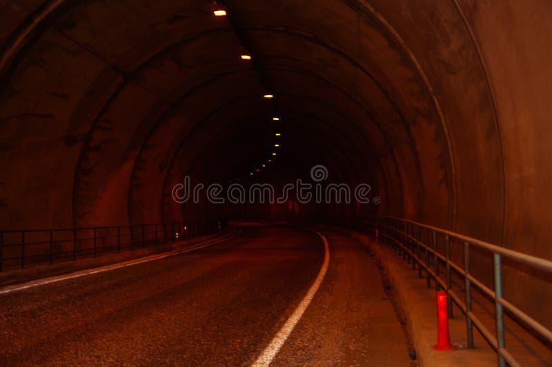Dark car tunnel illuminated by lamps. stock photo