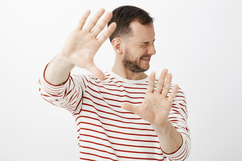 Turn light off. Portrait of displeased uncomfortable male model in casual outfit, pulling palms at camera and turning. Face to hide from shiny light or punch stock photos