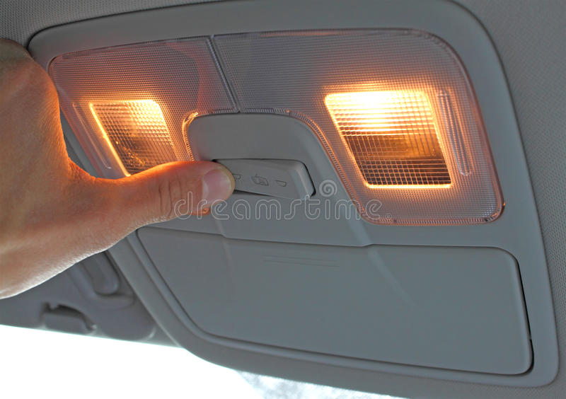 Turn on light switch in the car. With hand royalty free stock photos