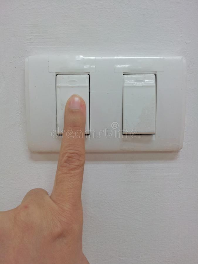 Turn off the light. Close up of the finger is turning off on light switch royalty free stock photography