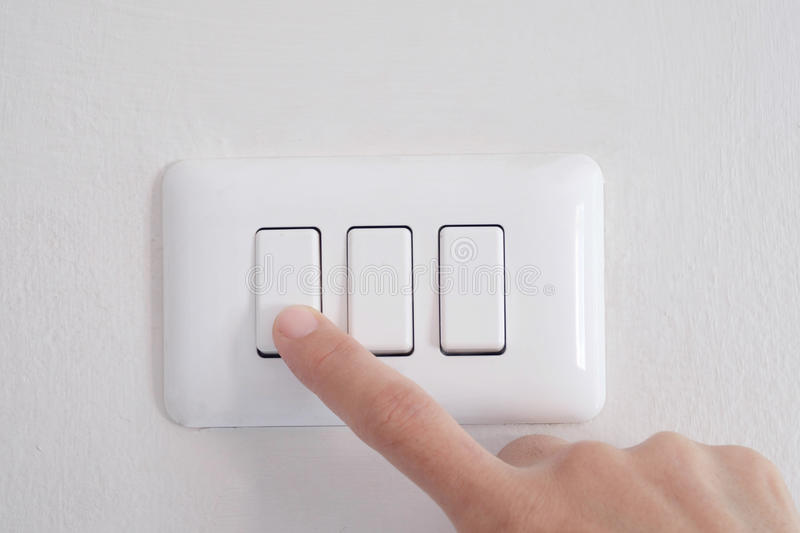 Turn off light. Finger turn off switch of light on wall royalty free stock image