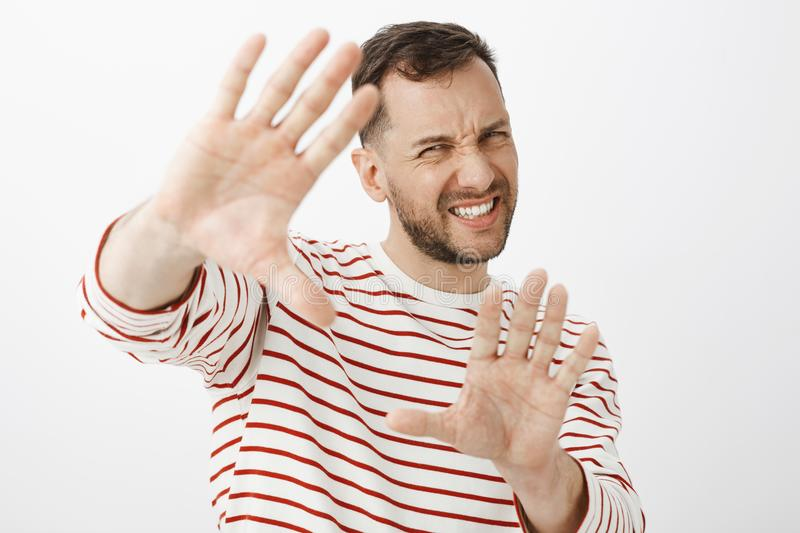 Turn off light it is to shiny. Displeased uncomfortable handsome adult man in striped outfit pulling hands towards. Camera to protect face, grimacing from royalty free stock image